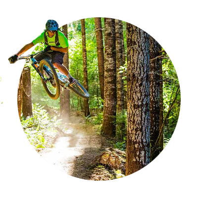 Airborne mountain biker maneuvers a curve amid tall fir trees on the Sandy Ridge Trail just east of Sandy, Oregon