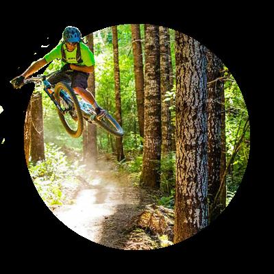 Airborne mountain biker maneuvers a curve amid tall fir trees on the Sandy Ridge Trail just east of Sandy, Oregon