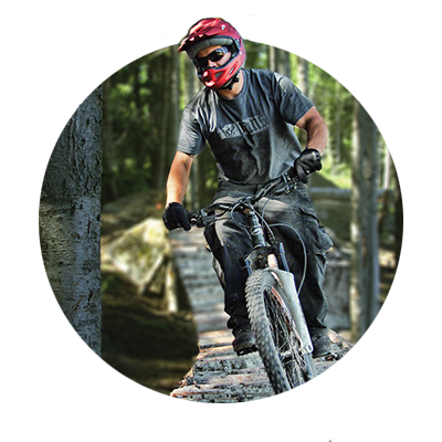 Mountain biker rides on narrow wooden plank path through forest at Skibowl's Adventure Park in Oregon's Mt. Hood Territory