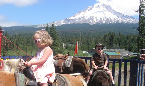 Mt. Hood can be seen in the background with children riding ponies in the sun at Mt. Hood Adventure Park at Skibowl in Mt. Hood Territory.