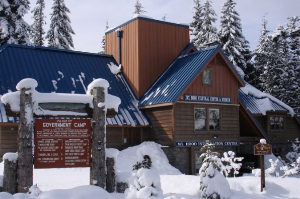 Snow slides down the steep blue metal roof of the Mt. Hood Cultural Center & Museum as snow covered the grounds and trees