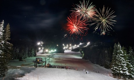 Night ski lights shine on the upper ski run as a crowd stands near base with three colorful fireworks bursting above them