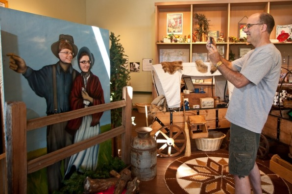 Two young teens pose behind a photo board of a pioneer couple as Dad takes their photo at End of the Oregon Trail Interpretive Center.