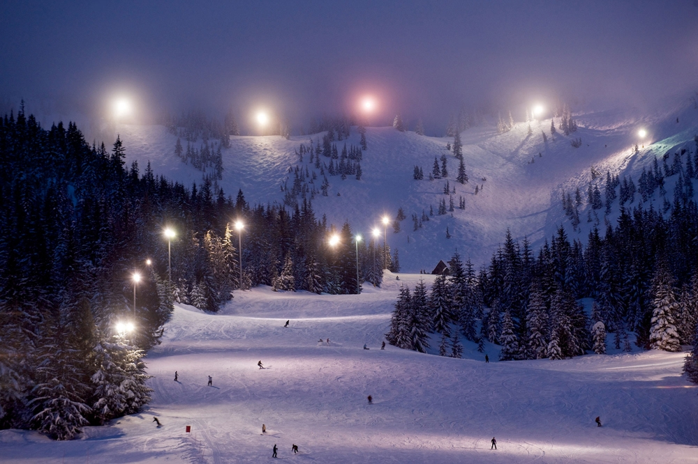 Large floodlights illuminate the upper bowl and lower ski run as skiers and boarders enjoy night skiing at Mt. Hood Skibowl