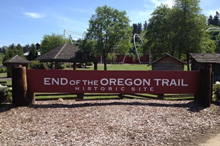 Large wooden entrance sign to End of The Oregon Trail Historic Site in Oregon City