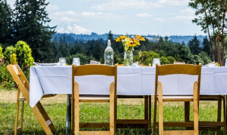Our Table Cooperative farm brunch table with white linen cloth, place settings and flowers set outside with Mt. Hood view.