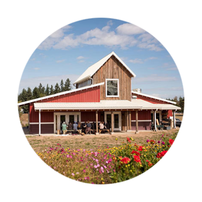 Circular photo of the barn style, red farm store with covered patio shielding people sitting at picnic table from the sun