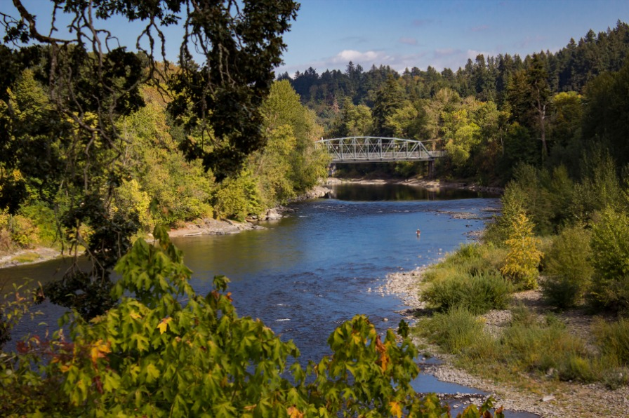 View of the Wild & Scenic Clackamas River with green trees, blue river and a bridge in distance in Oregon's Mount Hood Territory