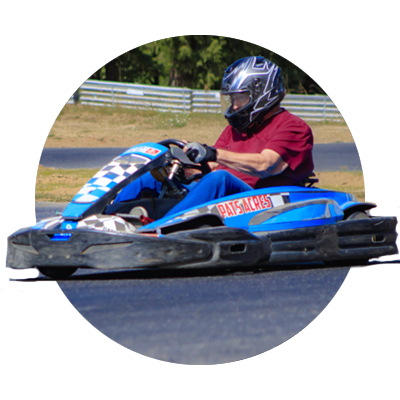 Male Go-Kart driver on blue go-kart races around the track at Pat's Acres in Canby in Oregon's Mt. Hood Territory