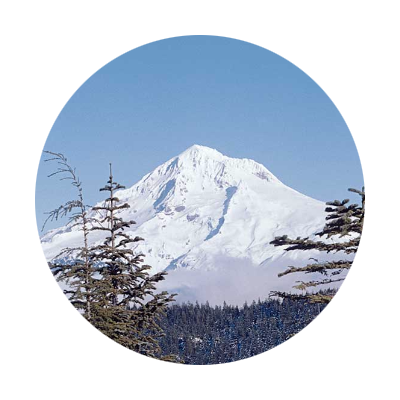 Circular photo of snow covered Mt. Hood with Mt. Hood National Forest foothills in forefront