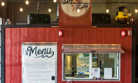Side view of The Perky Pantry red food cart with large menu sign covering door and serving window with condiment shelf