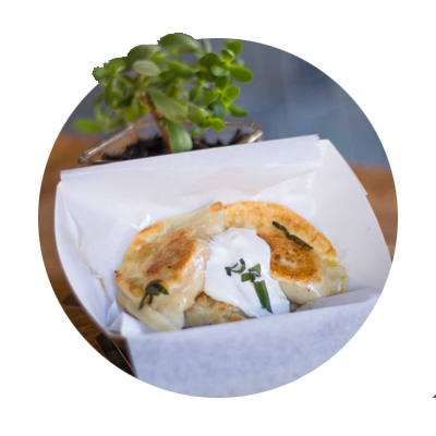 Serving of golden brown pierogis with sour cream at The Perky Pantry, Oregon City's first food cart