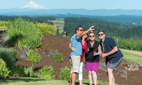 Four friends all in sunglasses on a sunny day take a Mt. Hood selfie from the lawn at Petes Mountain Vineyard in West Linn