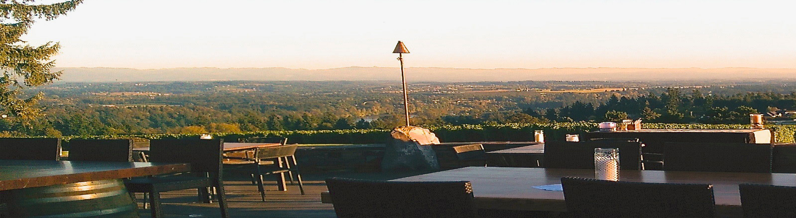Tabletops resting on wine barrels fill Pete's Mountain Winery patio overlooking Willamette Valley in Mt. Hood Territory