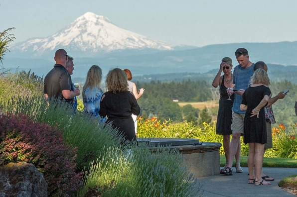 Nine guests on the patio at Pete's Mountain Vineyard enjoying glasses of wine as they gaze out across valley at Mt. Hood.