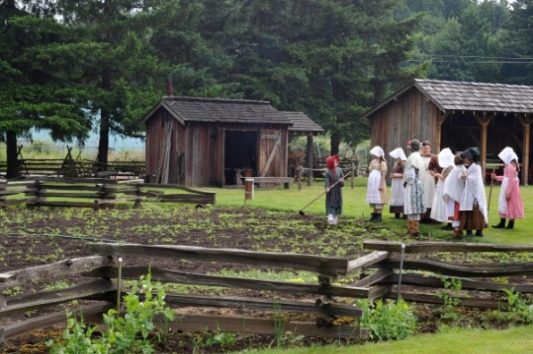 Girls dressed in pioneer garb with white bonnets tend garden enclosed in split rail fence at historic Philip Foster Farm