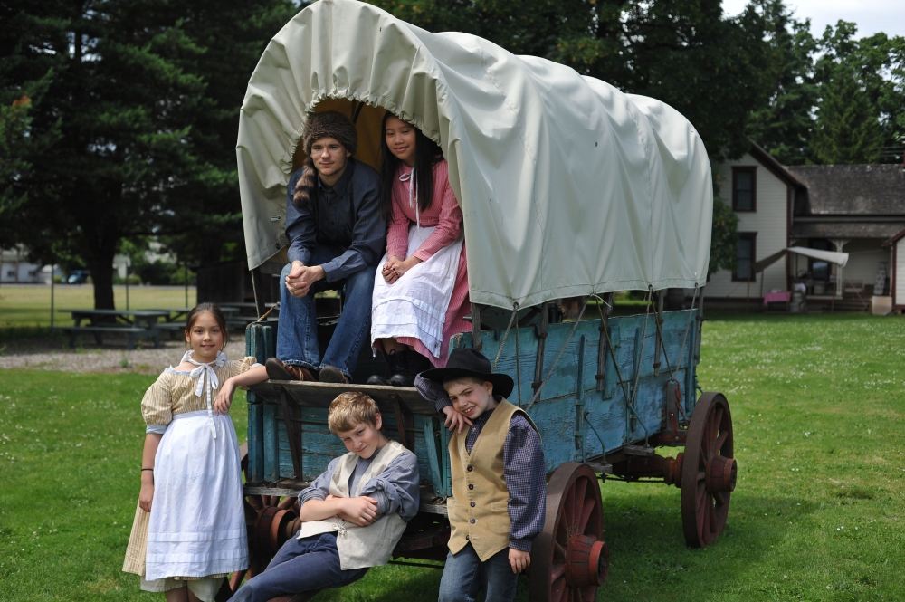 Six young children dressed in pioneer clothing posing on an a period blue wagon with white cover at Philip Foster Farm in Oregons Mount Hood Territory.