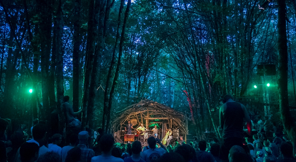 100+ Pickathon concert goers sitting in woods at night listening to musical group play from a domed stage of tree branches