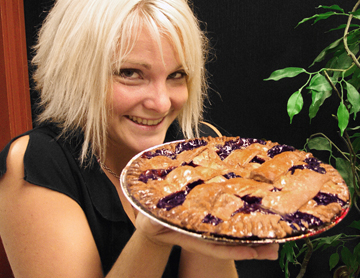 Young blonde haired woman holding a large huckleberry pie with lattice crust