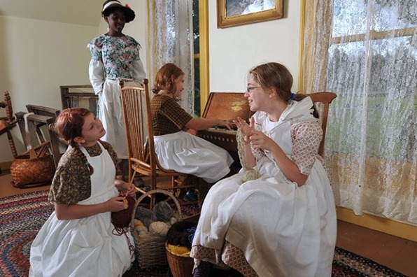 Young pioneer women reenactors do their knitting while one plays the piano in the farmhouse on Philip Foster Farm.