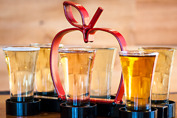 Portland Cider Co.'s Clackamas Pub & Cideery tasting flight of 6 ciders in black carrier with large red apple shaped handle