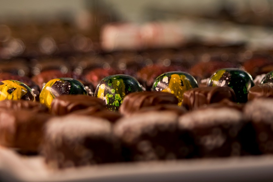 Row of colorful gold, green and white speckled truffles surrounded by out-of-focus chocolates at Puddin' River Chocolates