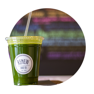 Circular photo of plastic To Go cup filled with a healthy, fresh green juice concoction from West Linn's renew Juice Co.