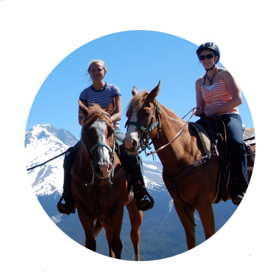 Two young women enjoy a horseback ride on a clear summer day with spectacular views of Mt. Hood.