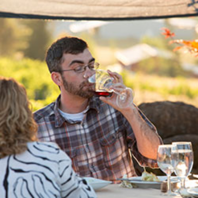 gentleman drinking wine with the valley in the background at a farm to table wine dinner event in Oregon's Mt. Hood Territory