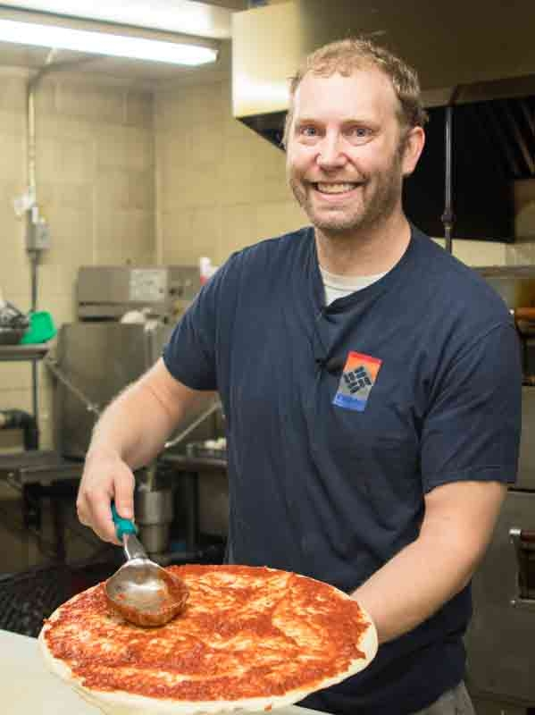 Ivy Bear owner Scott adding sauce to pizza dough