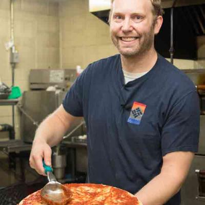 Ivy Bear Pizzeria owner Scott adding sauce to pizza dough