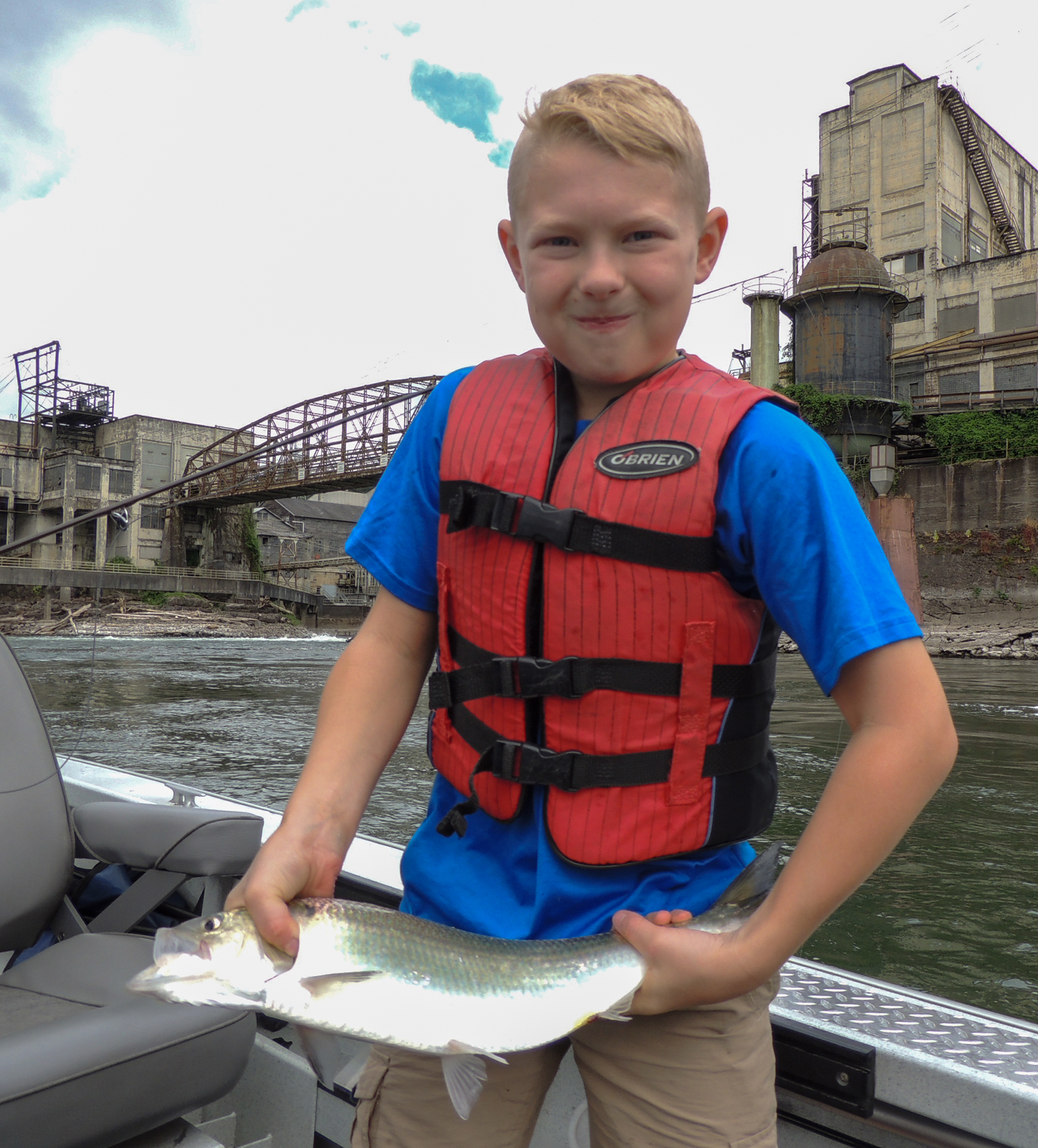 Young fair-haired boy in red lifejacket standing in boat on the Willamette River in Oregon City shows off his salmon catch.
