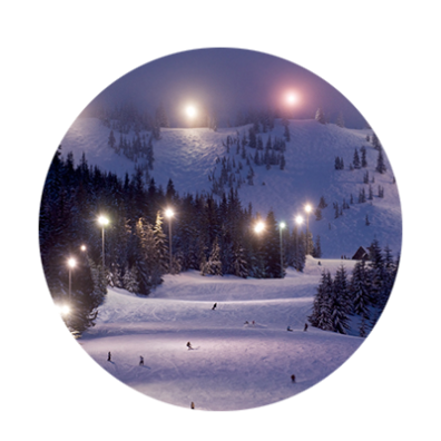 Floodlights light up the upper and lower bowls at Mt. Hood Skibowl as night skiers and boarders race down the mountain.