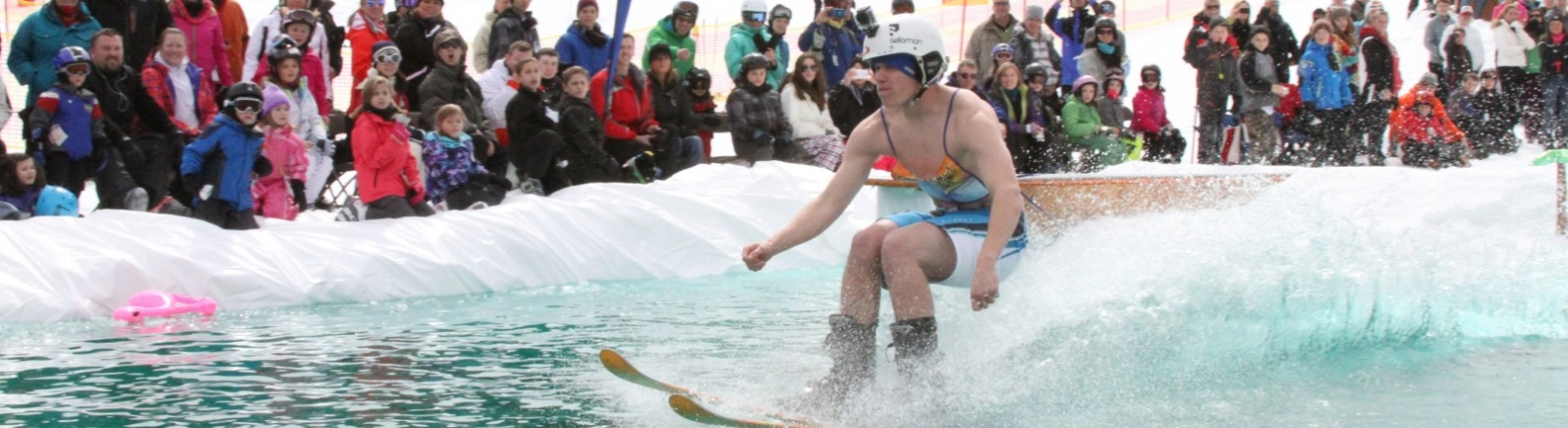 Crowd cheers on Mt. Hood Skibowl's Snow Beach Festival contestant as he tries skiing across pond of freezing water