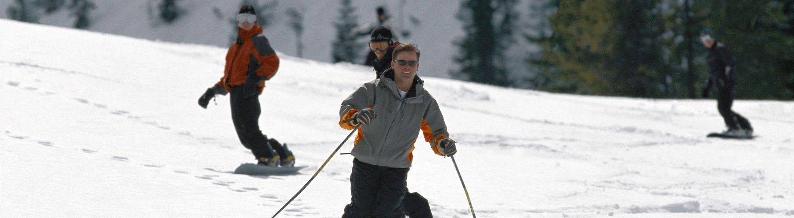 Downhill skier and 3 snowboarders winding their way down run at Mt. Hood Skibowl in Oregon's Mount Hood Territory