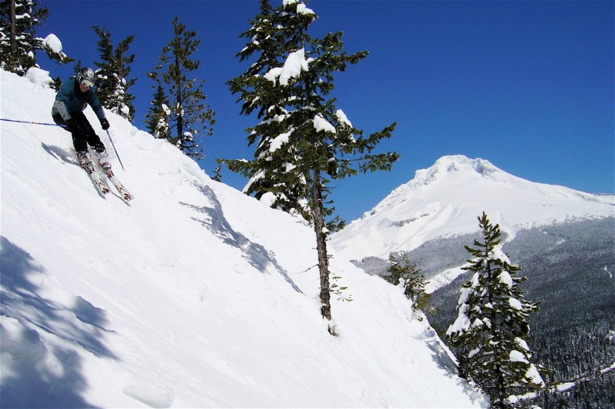 Downhill skier descending one of Skibowl's steep hillside runs with view of snow covered Mt. Hood against a deep blue sky