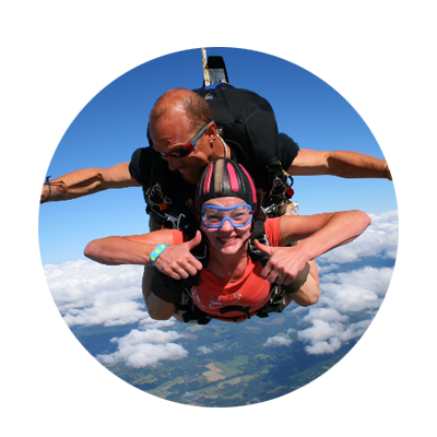 Female skydiver gives the thumbs up sign with her male instructor above her in a tandem jmp high above the Willamette Valley