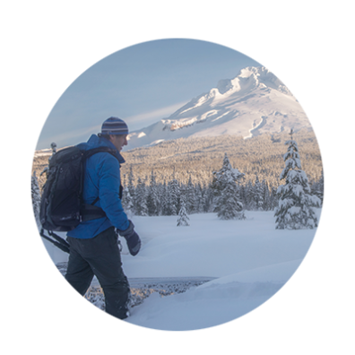 Snowshoer with large backpack makes his way across a nowcoverd meadow as Mt. Hood and National Forest fill his view.