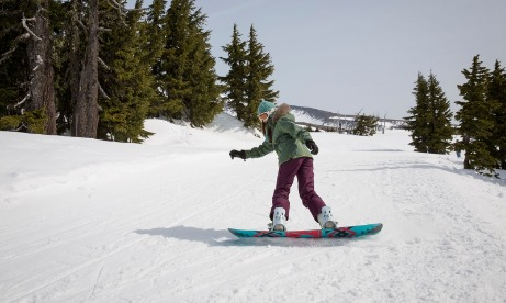 Female snowboarder tests her skills in the middle of a trail at Timberline Ski Area on Mt. Hood