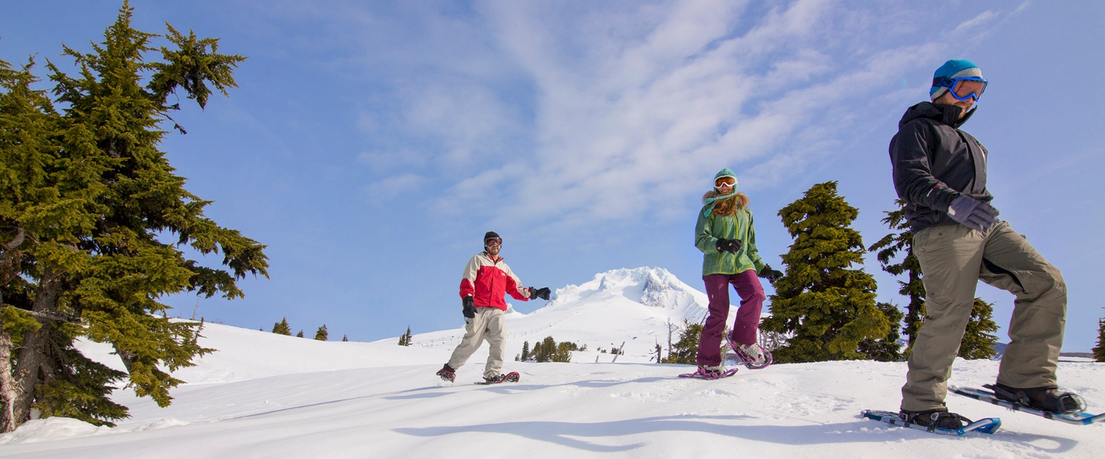Three snowshoers cross over a ski run as they make their way downhill with Mt. Hood behind them at Timberline Ski Area