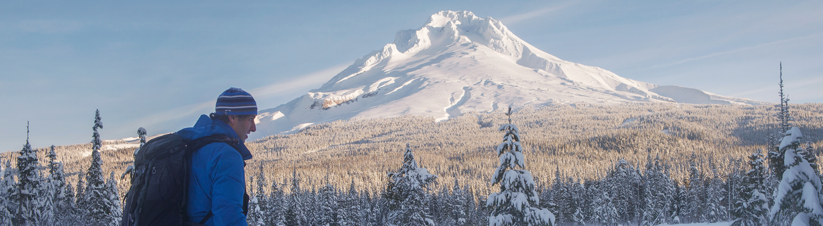 Mt. Hood in all its white glory is viewed by a snowshoer with a large backpack crossing a forest meadow near Trillium Lake
