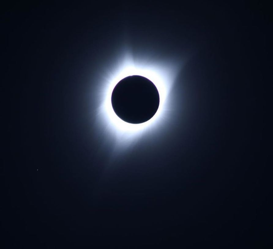 solar eclipse with black background white glow around black eclipse moon