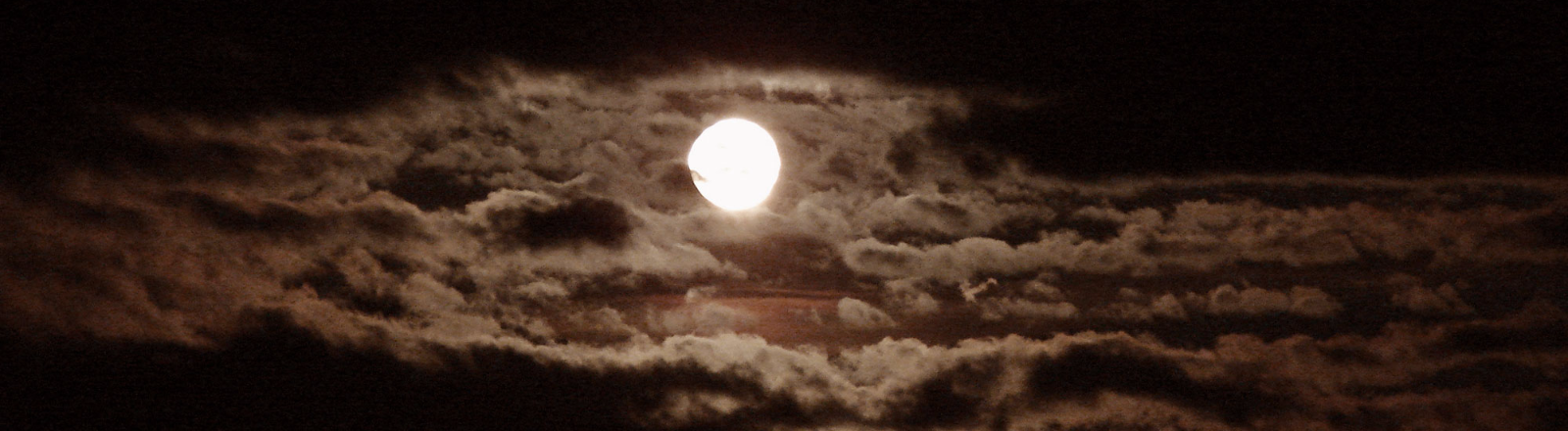 Full moon emerges revealing a sky full of clouds on a dark black spooky night