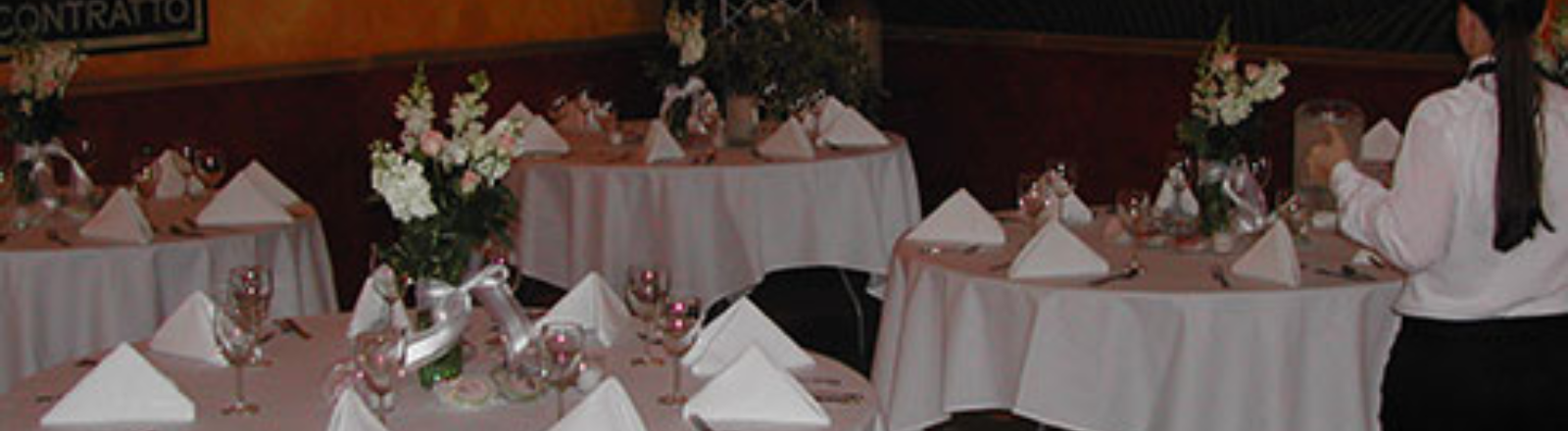 Tables set with white linens and flower bouquets on each in the private event room at Canby's St. Josef's Vineyard and Winery