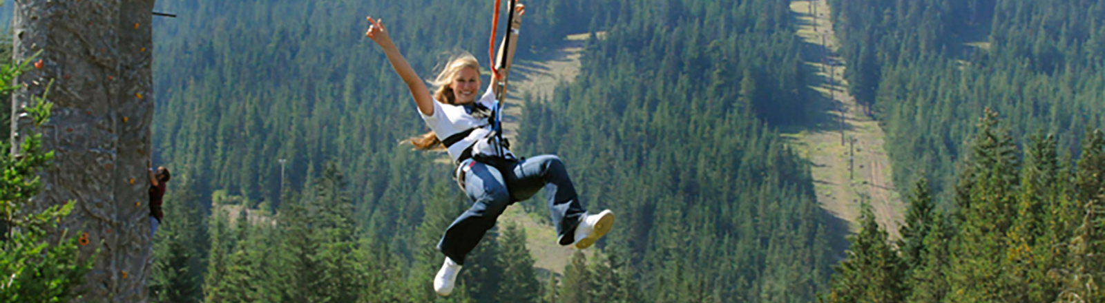 Female glides through the air on a zipline at Mt. Hood Adventure Park at Skibowl in Mt. Hood Territory.