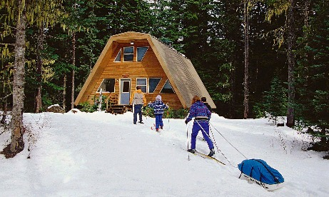 Four family members XC skiing up to the front of their vacation rental in the forest