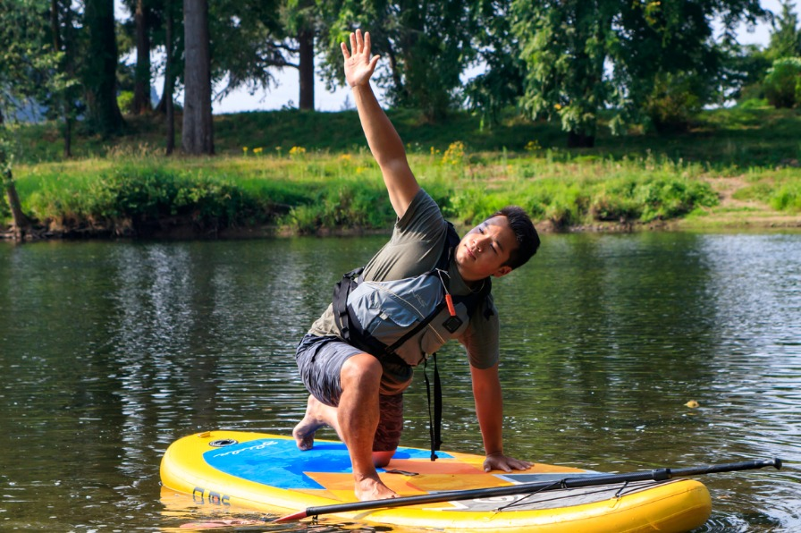 Paddleboarder doing a yoga pose at Stand up paddleboard yoga