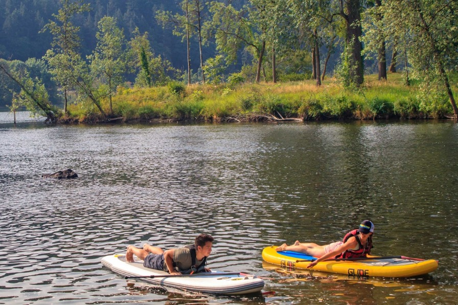 Male and female instructors demonstrate stand-up paddleboard yoga on inflatable boards at West Linns Willamette Park