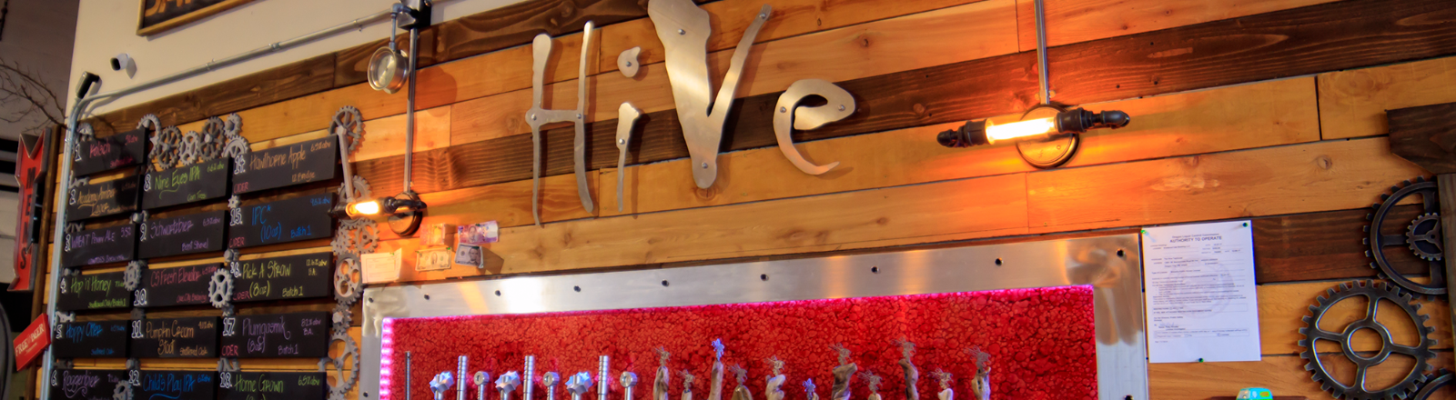 HiVe Taphouse's wall of cider and beer taps and menu board with HiVe logo done in polished metal letters above the taps