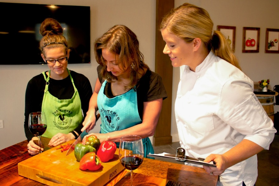During a cooking class, the female head chef at Middleground Farms teaches two young women the proper way to cut vegetables